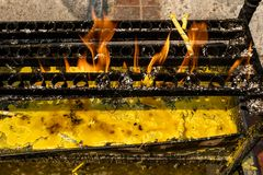 Yellow candles burning on black metal holder with orange flame and yellow candle tears underneath in a Buddhist temple. Yellow candles burning on black metal royalty free stock photo