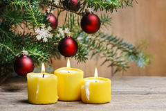 Yellow candles in front of christmas tree. Royalty Free Stock Photography