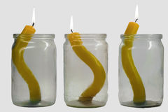 Yellow candles. Three glass jars with candles inside Royalty Free Stock Image