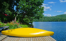 Yellow canoe on dock beside lake in summer time Royalty Free Stock Image