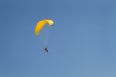 Yellow Canopy Paraglider. Man flies through a blue sky on a powered parglider with a yellow canopy Stock Image
