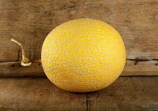 Yellow cantaloupe melon on the wooden background Royalty Free Stock Photos