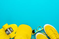 Yellow cap, sunglasses, sneakers, mini cruiser on blue background and copy space. Top view of yellow modern teenage accessories. Flat lay image of yellow stock images