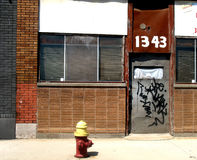 Yellow capped fire hydrant. In front of an abandoned building Stock Photos