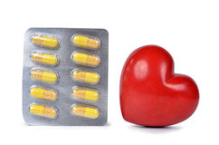Yellow capsule pills with heart Stock Photography