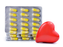 Yellow capsule pills with heart Stock Image