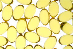 Yellow Capsules. Close up of gel yellow capsules containing high concentrate fish oil, rich in essential fatty acids Stock Image