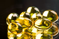 Yellow capsules. Photo of yellow transparent capsules on the black background Royalty Free Stock Photography