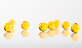 Yellow capsules on white Royalty Free Stock Photo