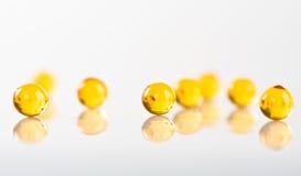 Yellow capsules on white Royalty Free Stock Photo