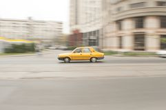 Yellow car blurred background Stock Photos
