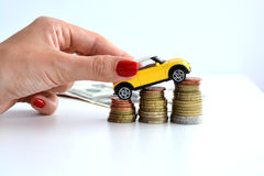 Yellow car climbing on pile of coins suggesting increase of sales trend Stock Photos