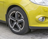 Yellow car closeup - front wheel with light alloy rim Royalty Free Stock Photos
