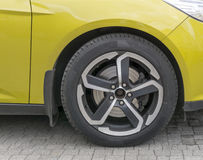 Yellow car closeup - front wheel with light alloy rim. Yellow sports car closeup - front wheel with light alloy rim Royalty Free Stock Photography