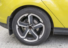 Yellow car closeup - rear wheel with light alloy rim. Yellow sports car closeup - rear wheel with light alloy rim Stock Photos