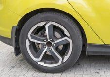 Yellow car closeup - rear wheel with light alloy rim Stock Photos