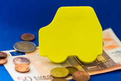 Yellow Car Cut Out with Euro Currency on Blue Stock Photos