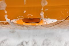 Yellow car door handle covered with shampoo and foam when washed stock photo