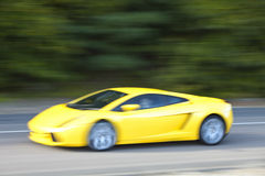 Yellow car driving fast on country road Stock Photos