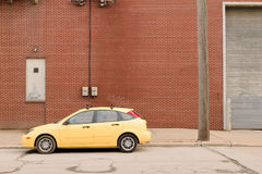 Yellow car on empty industrial concrete street. An abstract capture of a yellow car on empty industrial concrete urban city street Royalty Free Stock Photos