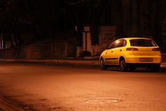 Yellow car in empty night street Stock Image