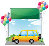 A yellow car and a green signage along the street Royalty Free Stock Photography