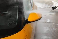 Yellow car high pressure water washing at carwash station. Jet w royalty free stock images