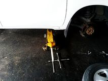 Yellow car lift jack lifting white car during fixing, maintenance or change new brake with half of tire at garage. With copy space royalty free stock photography