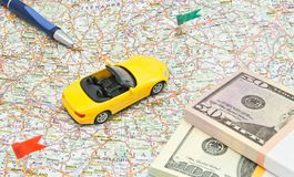 Yellow car, money and pen on map Stock Photography
