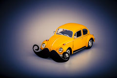 Yellow car with mustache, beetle on white Royalty Free Stock Photos