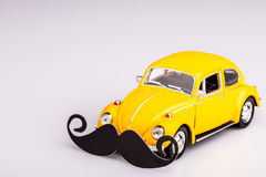 Yellow car with mustache, beetle on white Royalty Free Stock Images