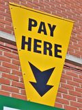 Yellow car parking sign with an arrow and text pay here royalty free stock photo