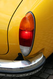 Yellow car, rear light and bumper. Details of a yellow car, rear light and bumper Royalty Free Stock Photo