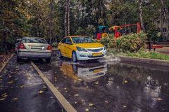 Yellow car rides in the yard on a wet road in the rain . Beautiful splashes of water from under the wheels.