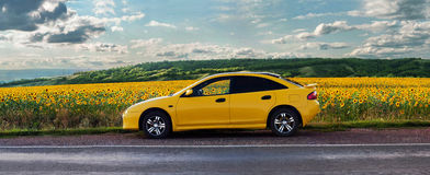 Yellow car on the road. Orenburg, Russia-July 2015: Yellow car on the road along the sunflower field Stock Photos
