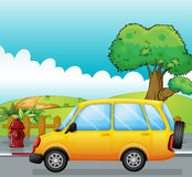 A yellow car running at the street Royalty Free Stock Photos