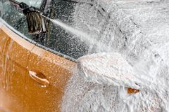 Yellow car side mirror completely covered with thick shampoo foam, more spraying from the brush, when cleaned in carwash. stock photos