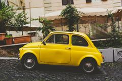 A yellow car in a small street in Rome royalty free stock photography