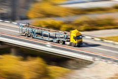 Yellow car transporter moving fast at the bridge Royalty Free Stock Photos