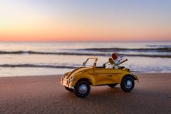 Yellow car with two surfboards on the beach. Yellow vintage car with two surfboards on the beach at sunset Stock Photos