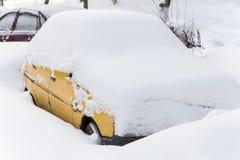 Yellow car under snow Royalty Free Stock Photos