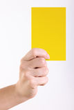 Yellow card. Woman hand with yellow card over white background royalty free stock image