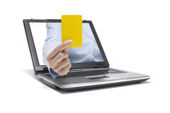 Yellow card. A hand reaches out of a laptop and shows a yellow card Royalty Free Stock Photography