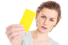 Yellow card. A picture of a serious woman showing a yellow card over white background Stock Images