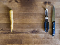 Yellow carrot, knife and peeler, meal preparation. Yellow carrot, knife and peeler on a wooden board, meal preparation scene, cooking background Royalty Free Stock Photography