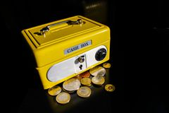 Yellow money box with numeric combination. Yellow cash box on black background, reflexes. security for your money with key lock and numeric combination and coin Stock Photography