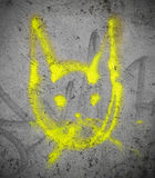 Yellow cat on the wall. Street art by unknown artist of a yellow creature resembling a cat Royalty Free Stock Photo