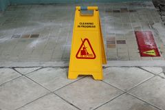 Yellow caution cleaning progress sign on the floor outdoors. Yellow caution cleaning progress sign on the ditry floor outdoors Royalty Free Stock Photography
