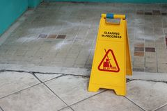 Yellow caution cleaning progress sign on the floor outdoors Stock Images