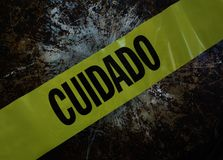 Yellow caution - cuidado tape. Yellow Cuidado Caution tape over textured background Stock Photography